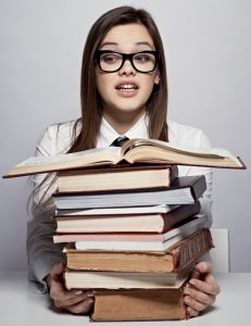Young student sitting at the table with heap of books